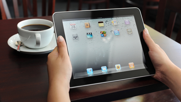 Hands holding iPad over table