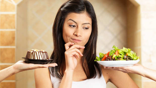 Woman choosing between salad and cake