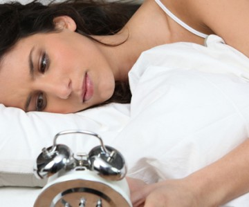Woman watching alarm clock