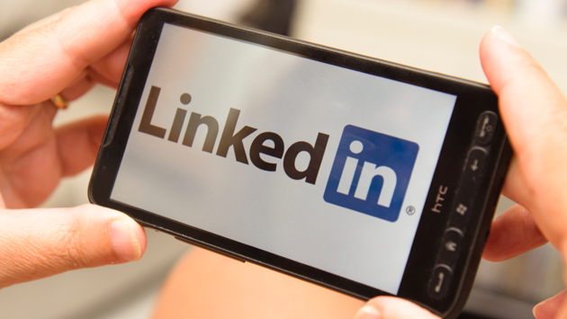 Holding a smartphone with LinkedIn Logo