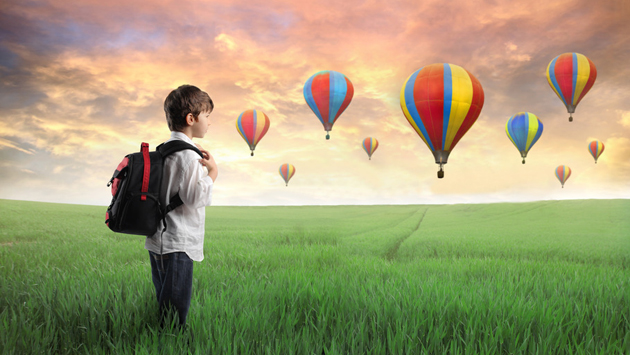 Boy standing in field with hot air balloons