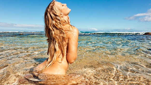 Woman bathing naked at beach