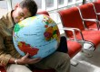 Man sleeping on globe in airport