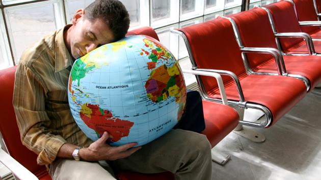 Man sleeping on globe in airport