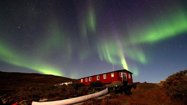 Aurora borealis glows over a hut