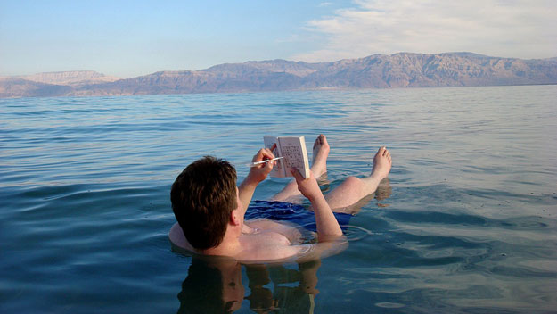 Man reading book while floating in Dead Sea