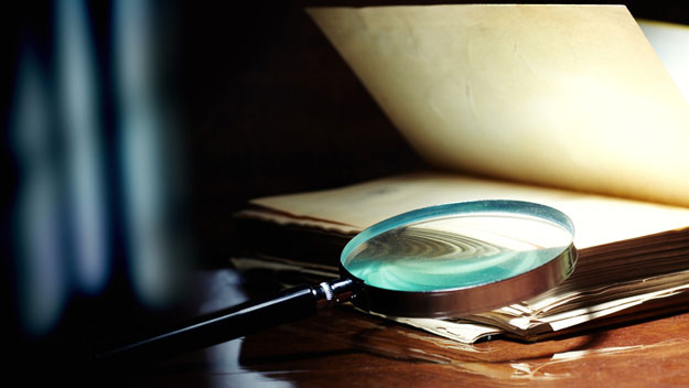 Old book and magnifying glass